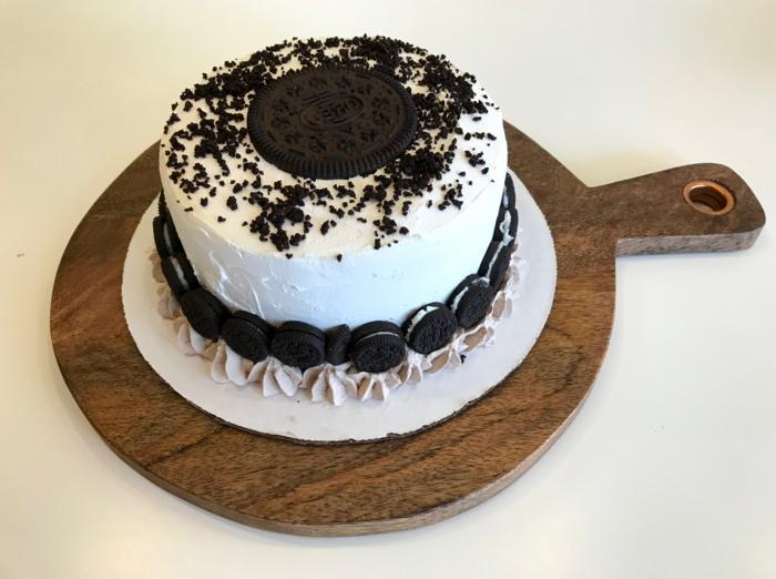 Torte mit weißer Creme, ein großer Keks in der Mitte, Mini Oreos an den Seiten, Oreo Cake