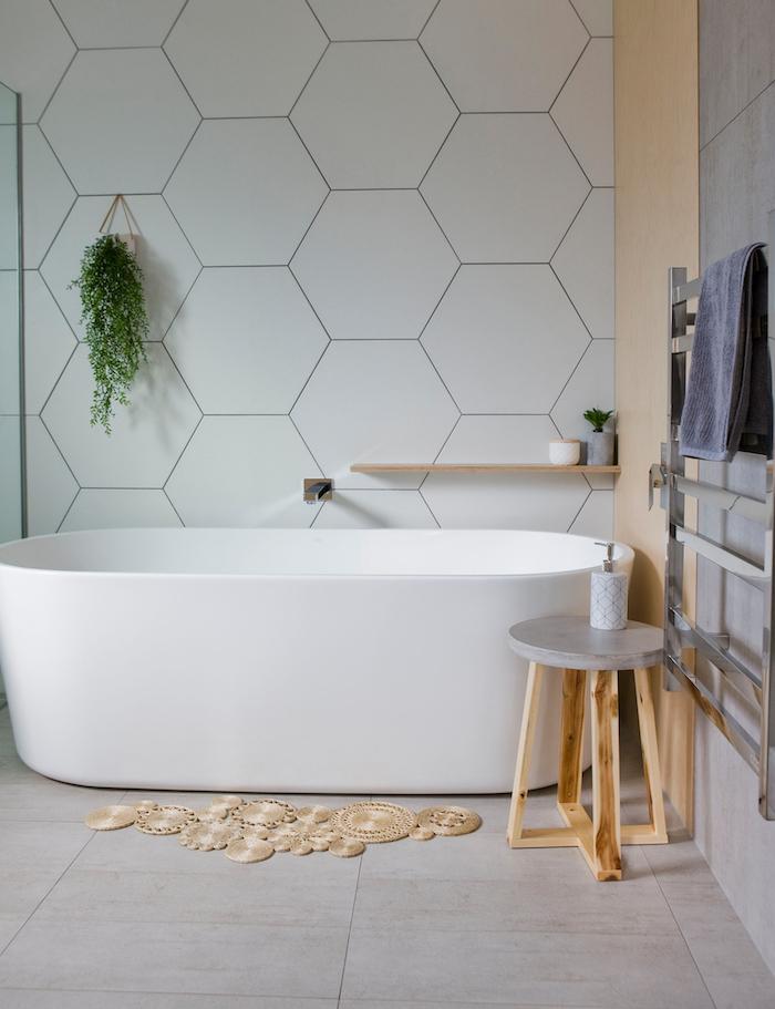 eine weiße wand aus weißen fliesen im badezimmer mit weißer freistehender badewanne und ein kleiner stuhl aus holz