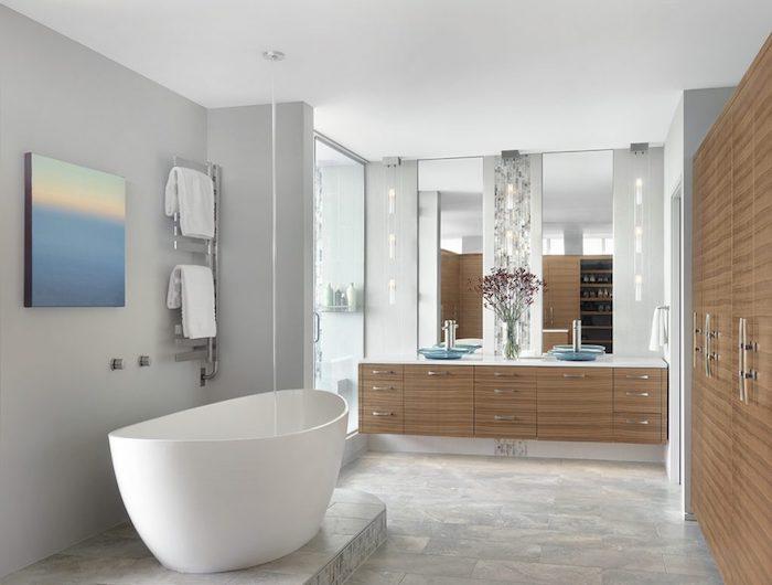 graue wände und eine kleine weiße freistehende badewanne und ein badezimmer spiegelschrank aus holz