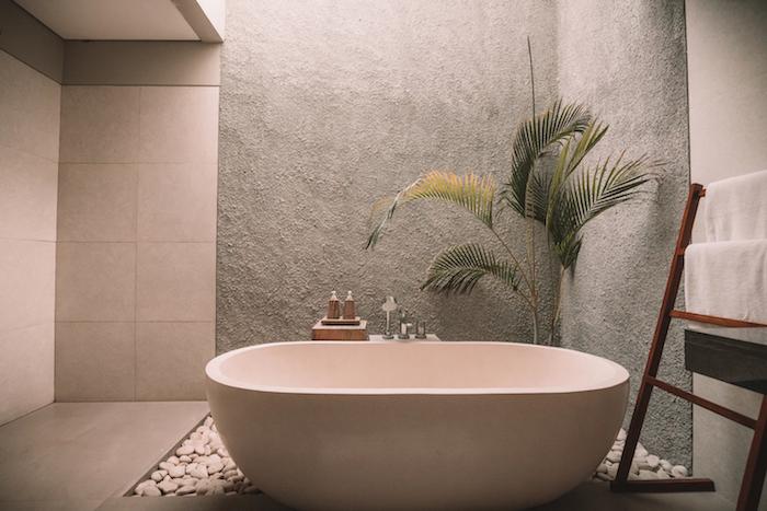 palme mit grünen blättern und eine kleine weiße freistehende badewanne und ein boden mit weißen steinen, outdoor dusche