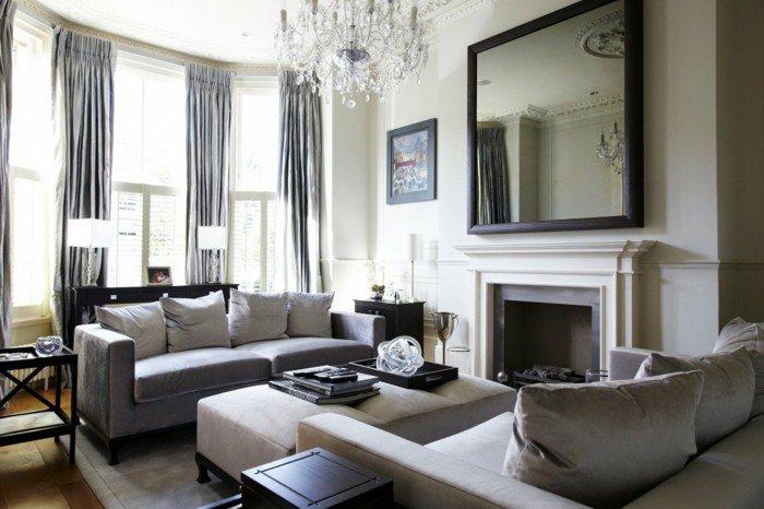 ein großer Spiegel, zwei Sofas, Kronleuchter aus Glas, Laminatboden, Wohnzimmer Weiß Grau
