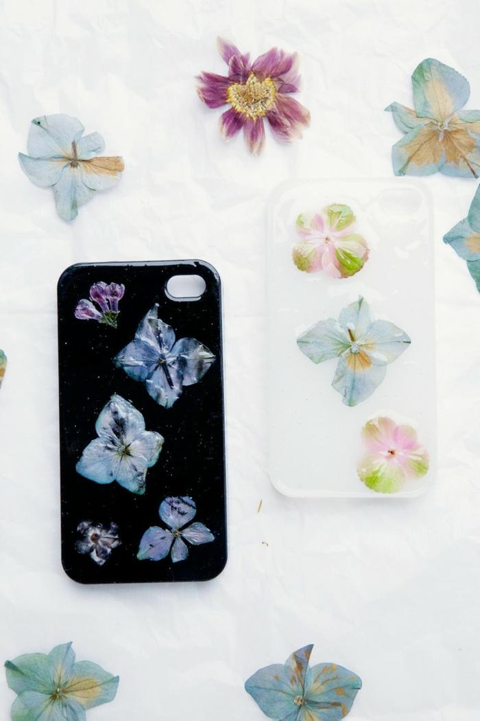 mit trockenen Blumen Handyhülle gestalten, Handyhülle in schwarzer Farbe und andere in weißer Farbe, blaue Blumen
