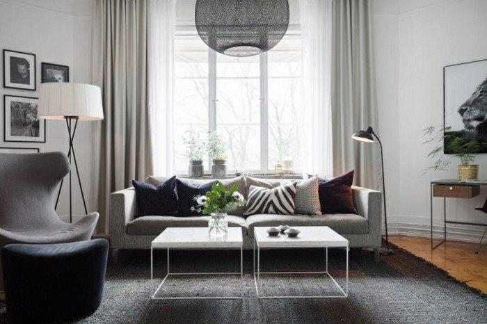 Wohnzimmer in Weiß Grau, ein weißes Sofa, ein grauer Sessel, zwei weiße Couchtische, schwarzer Lampenschirm