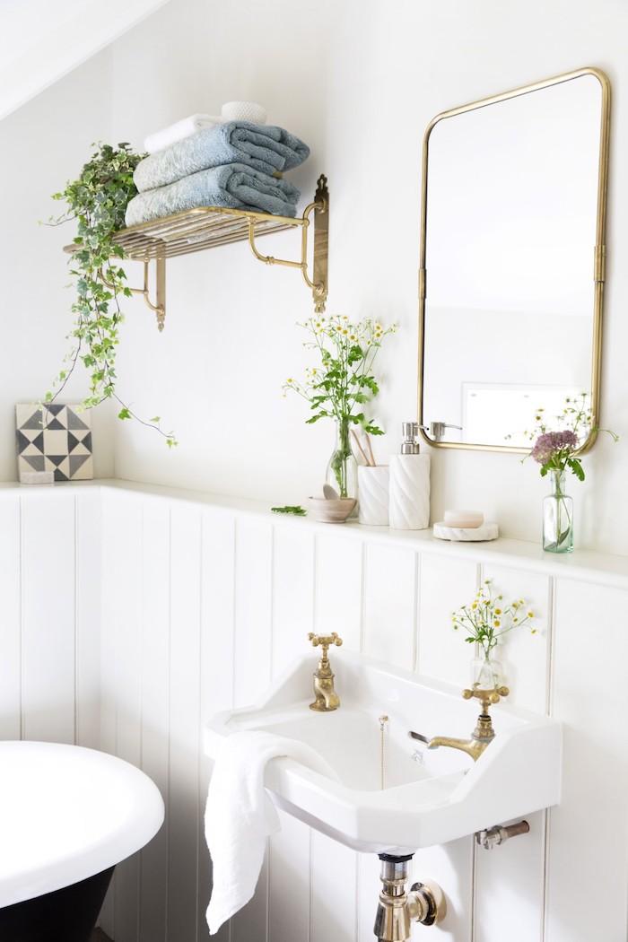 wände aus weißen badezimmer fliesen und ein spiegel und ein weißes waschbecken, blaue und weiße tücher