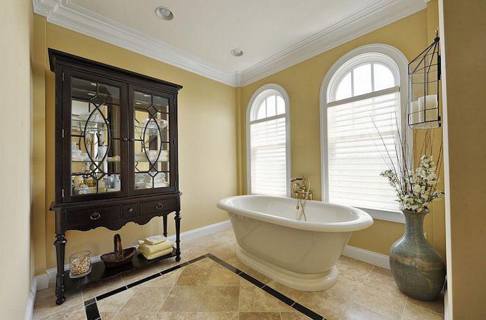 großes badezimmer mit gelben wänden und mit weißen fenstern und boden aus beigen badezimmer fliesen, eine graue vase mit weißen blumen und ästen