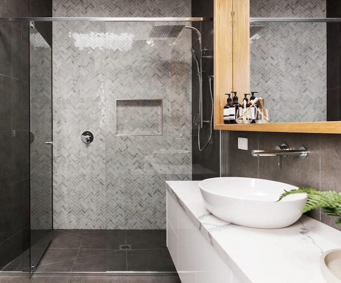 eine dusche aus metall im badezimmer mit wänden und boden aus schwarzen badezimmer fliesen, weißes waschbecken und ein großer spiegel
