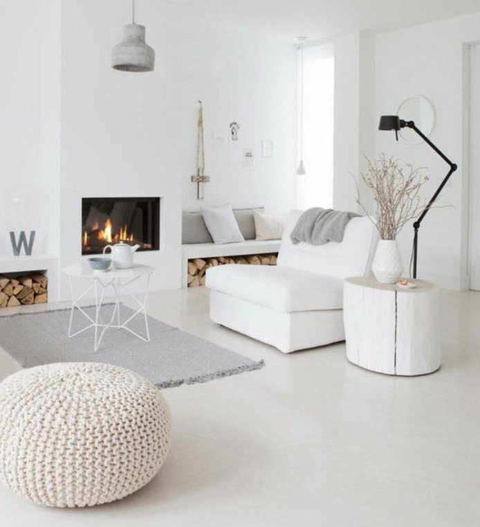 ein grauer Teppich, weißer Abstelltisch, Kamin mit warmem Feuer, ein weißer Sessel, Wohnzimmer Weiß Grau
