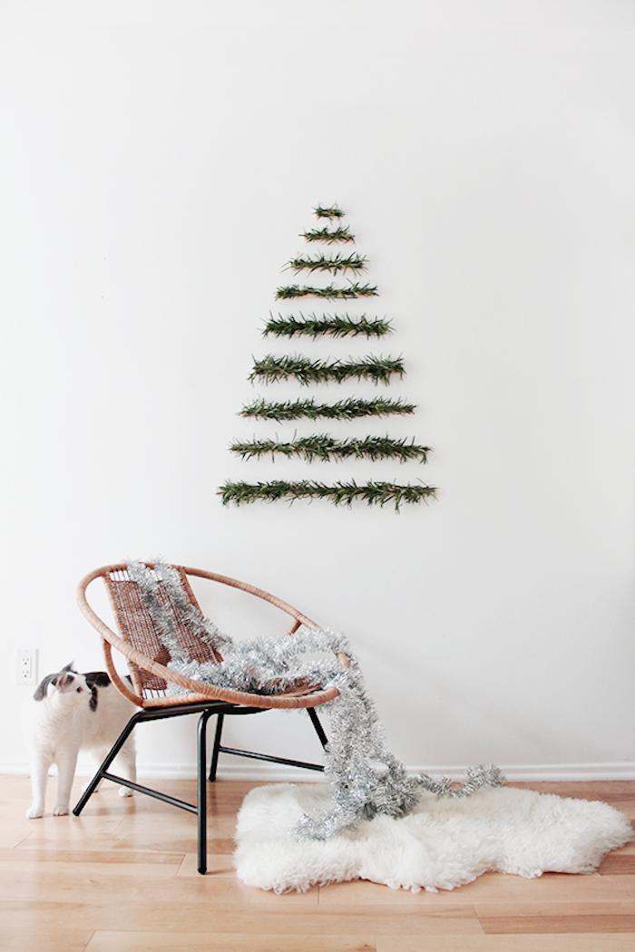 Weihnachtsbaum aus Tannengirlanden an der Wand gestalten, silberne Girlande auf dem Stuhl