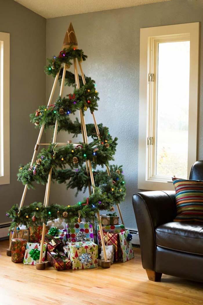 Tannengirlanden mit bunten Christbaumkugeln um Ständer wickeln, kreative Alternative zum Weihnachtsbaum