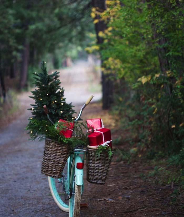 Fahrrad mit zwei Körben, Weihnachtsbaum und Geschenke darin, im Wald