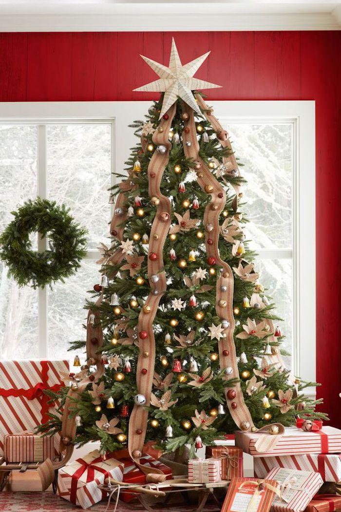 Großer Weihnachtsbaum geschmückt mit bunten Christbaumkugeln und Schleifen, schön verpackte Weihnachtsgeschenke unter dem Baum