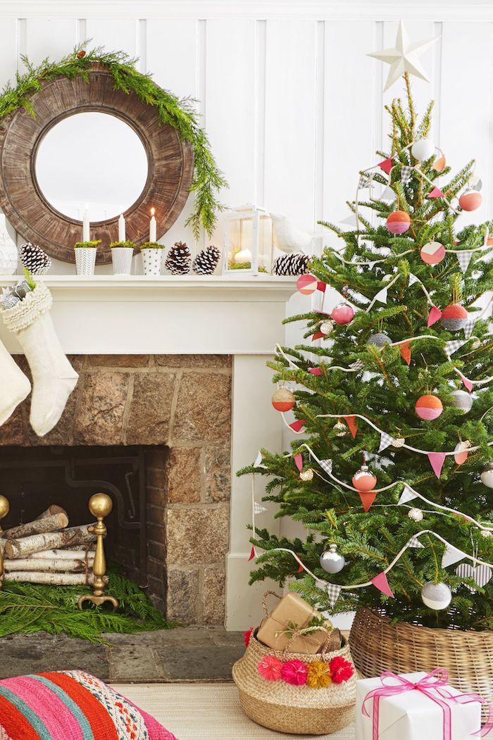 Weihnachtsbaum geschmückt mit bunten Christbaumkugeln und Girlanden aus Papier, Tannenzapfen und weiße Kerzen auf dem Kamin