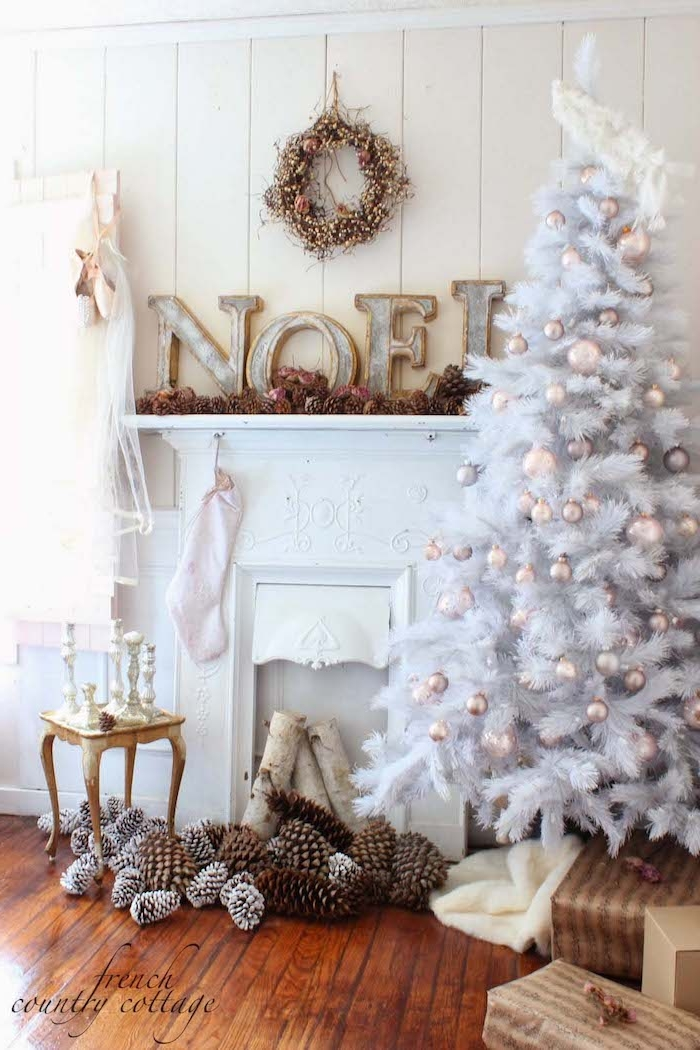 Weißer Weihnachtsbaum vor weißem Kamin, Zapfen am Boden, Weihnachtskranz und Weihnachtsstrumpf an der Wand