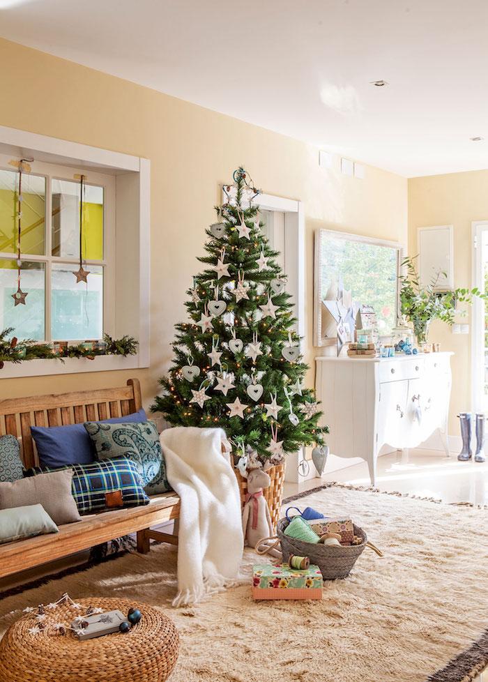 Echter Weihnachtsbaum geschmückt mit Sternen und Herzen, Dekokissen und weiße Deko auf Holzbank, Couchtisch aus Rattan