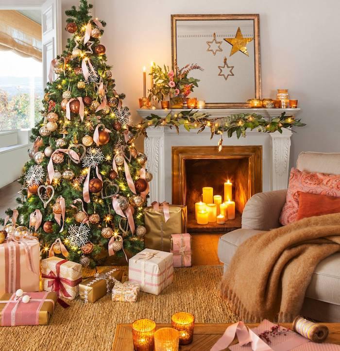 Weihnachtsbaum geschmückt mit goldenen Weihnachtskugeln und Schleifen, Kerzen im Kamin, viele Geschenke unter dem Baum, Dekokissen und kuschelige Decke auf dem Sofa, Teelichter auf dem Couchtisch und auf dem Kamin