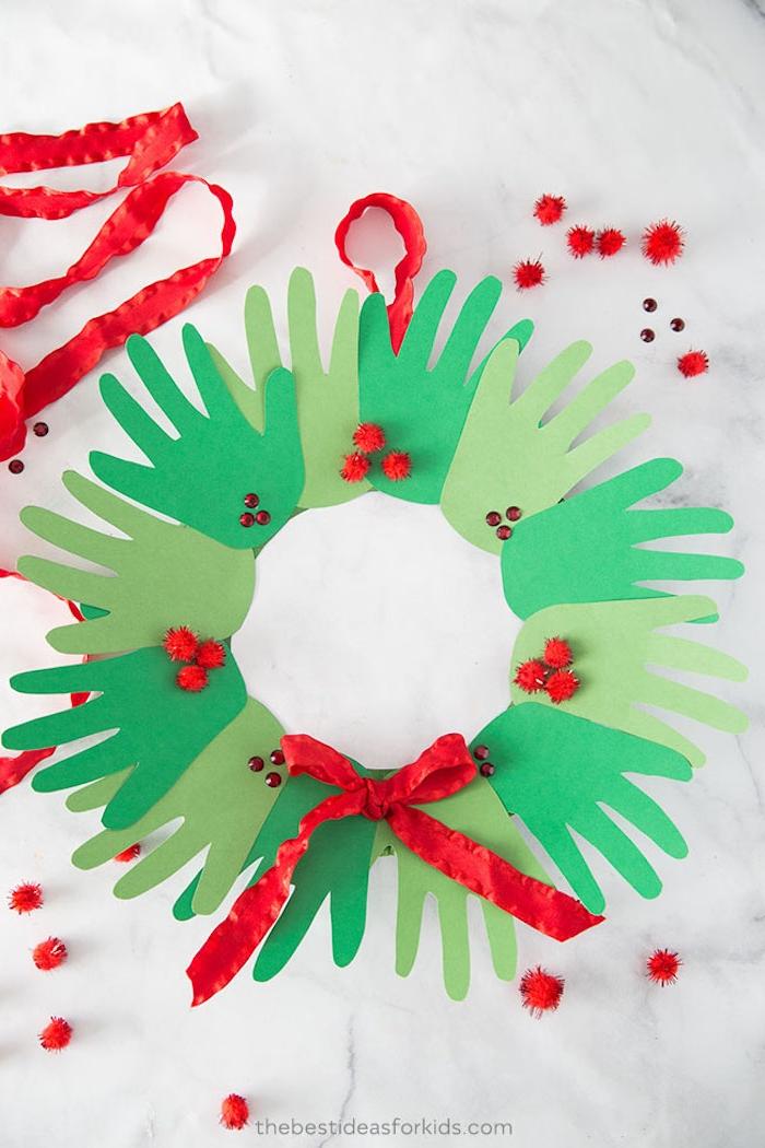 Weihnachtskranz aus grünem Karton selber basteln, Handabdrücke kleben, rote Schleife und Pompons