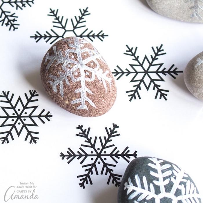 Schneeflocken mit weißer Farbe auf Steine malen, DIY Ideen für Weihnachtsstimmung zu Hause