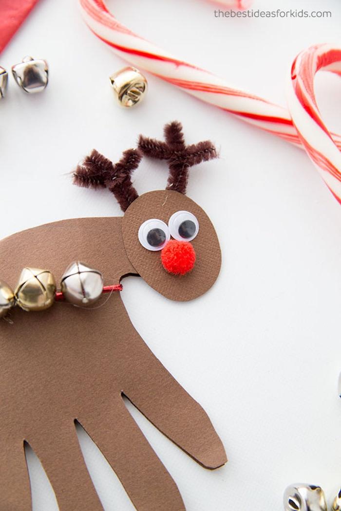 Basteln mit Papier zu Weihnachten, Rentier aus Handabdruck, Wackelaugen Pompon und Pfeifenreiniger kleben