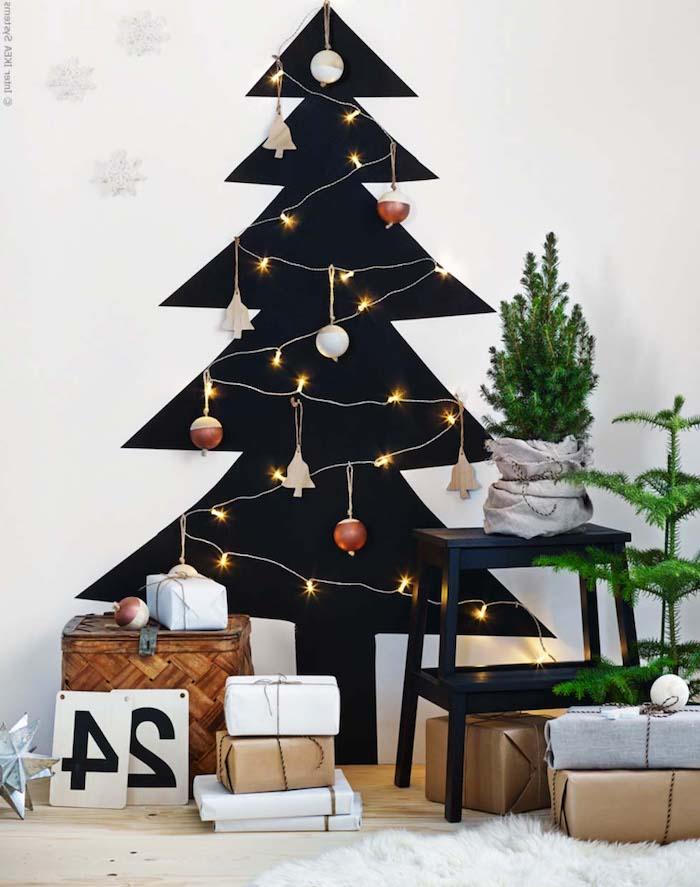 Weihnachtsbaum mit schwarzer Farbe an die Wand malen, Lichterkette und Anhänger an der Wand befestigen