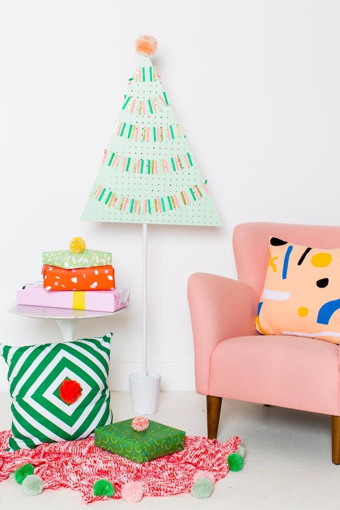 Wohnzimmer weihnachtlich dekorieren, Weihnachtsbaum aus Karton, drei Weihnachtsgeschenke, bunte Pompons