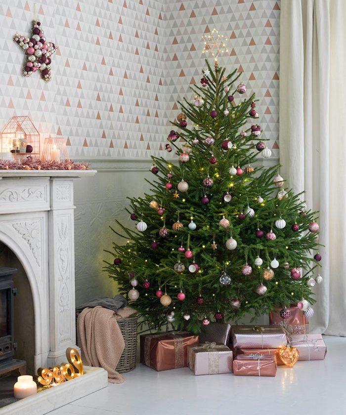 Echter Weihnachtsbaum geschmückt mit bunten Christbaumkugeln und Lichterkette, schön verpackte Geschenke unter dem Baum