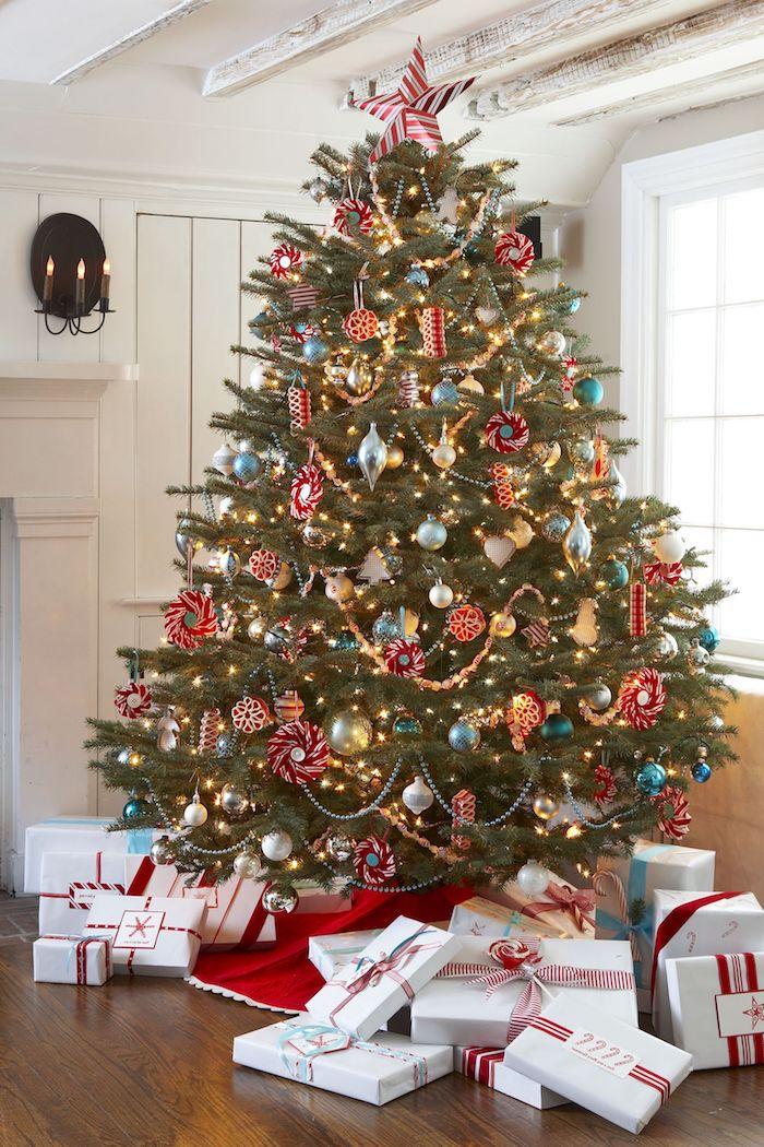 Großer Weihnachtsbaum mit viel Schmuck, Weihnachtsgeschenke verpackt mit weißem Geschenkpapier, dekoriert mit rotem Dekoband