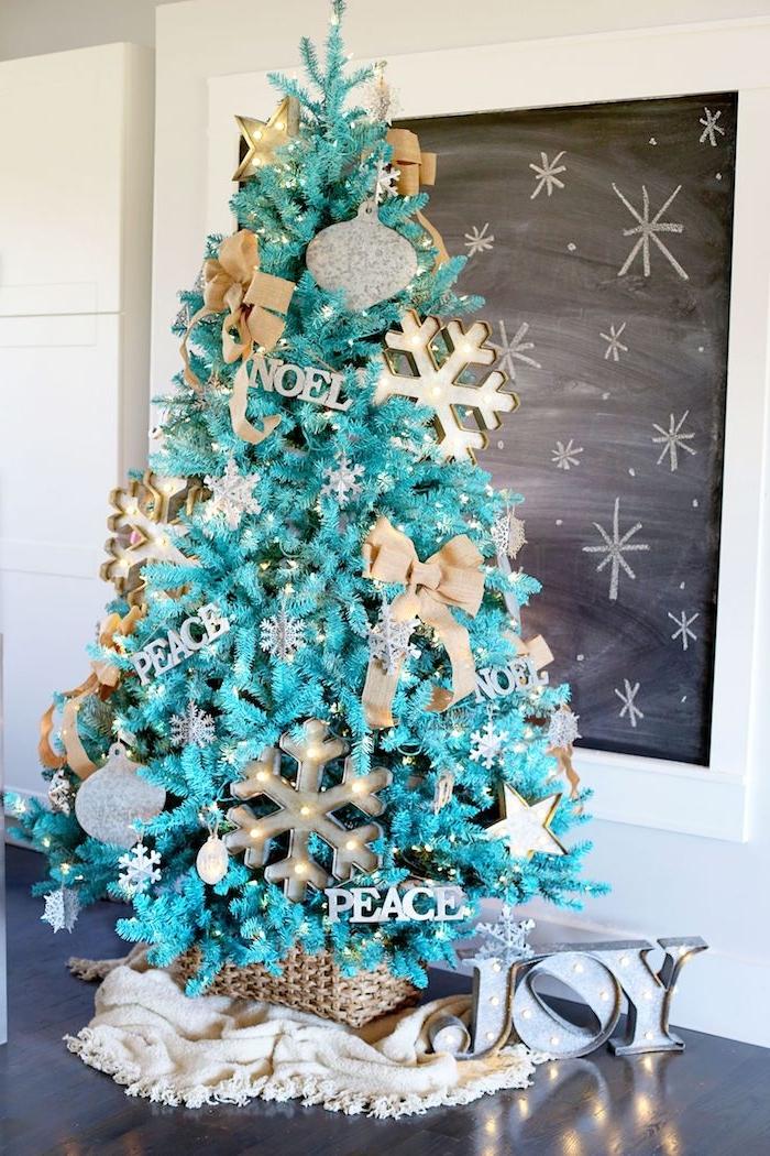 Künstlicher Weihnachtsbaum geschmückt mit Schleifen und Schneeflocken, in Rattankorb, weiße kuschelige Decke unter dem Baum