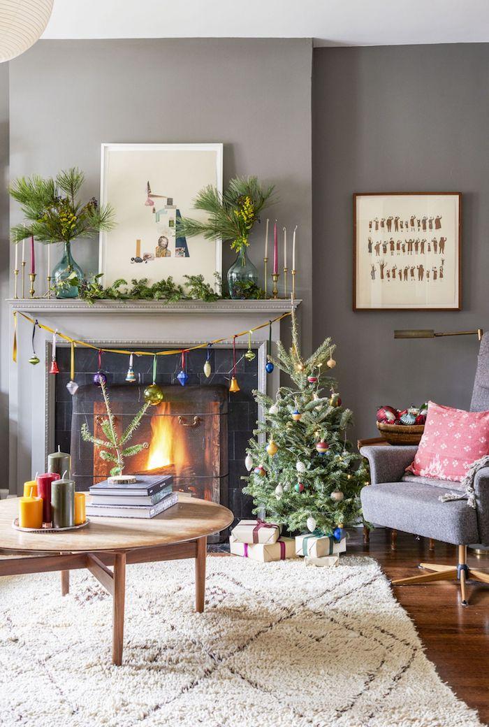 Kleiner Christbaum dekoriert mit Christbaumkugeln, Girlande mit Glöckchen am Kamin, runder Couchtisch, grauer Sessel