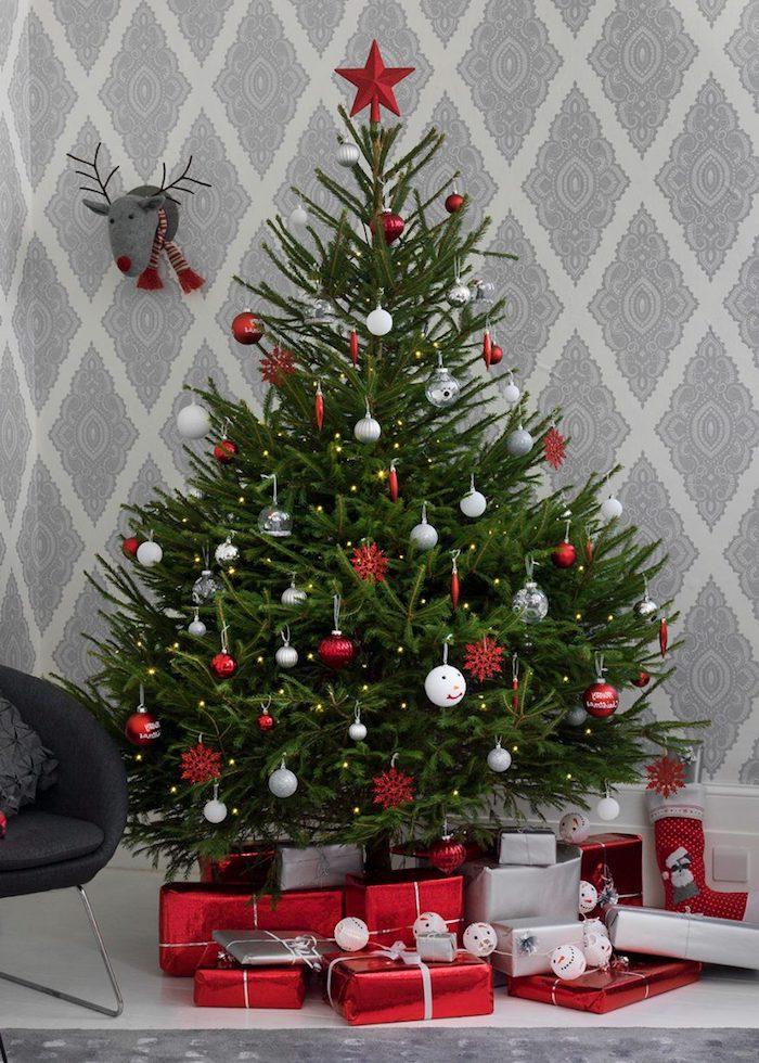 Echter Weihnachtsbaum geschmückt mit roten und weißen Christbaumkugeln, viele Geschenke unter dem Baum