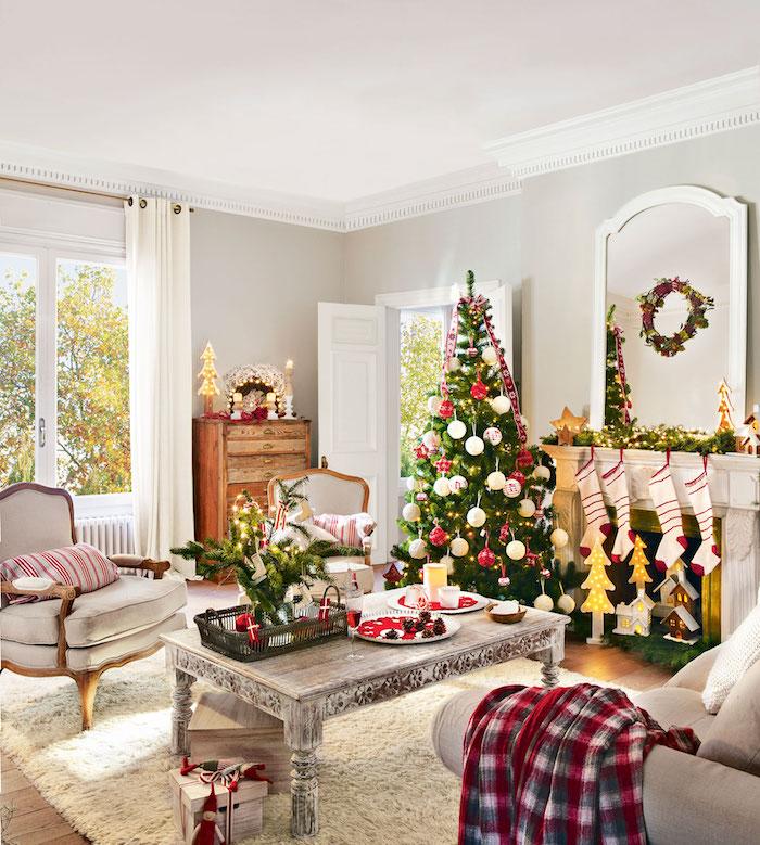 Wohnzimmer weihnachtlich dekoriert, Christbaum mit weißen und roten Christbaumkugeln, Weihnachtsstrümpfe am Kamin