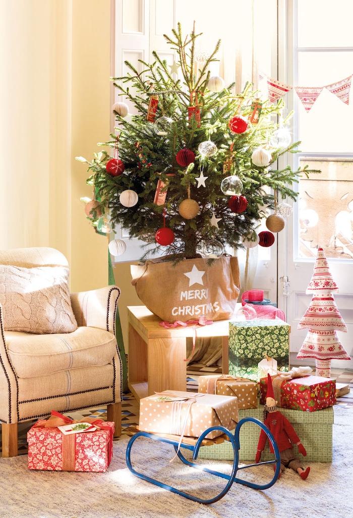 Kleiner Weihnachtsbaum in Geschenktüte, rote und weiße Christbaumkugeln, bunt verpackte Weihnachtsgeschenke