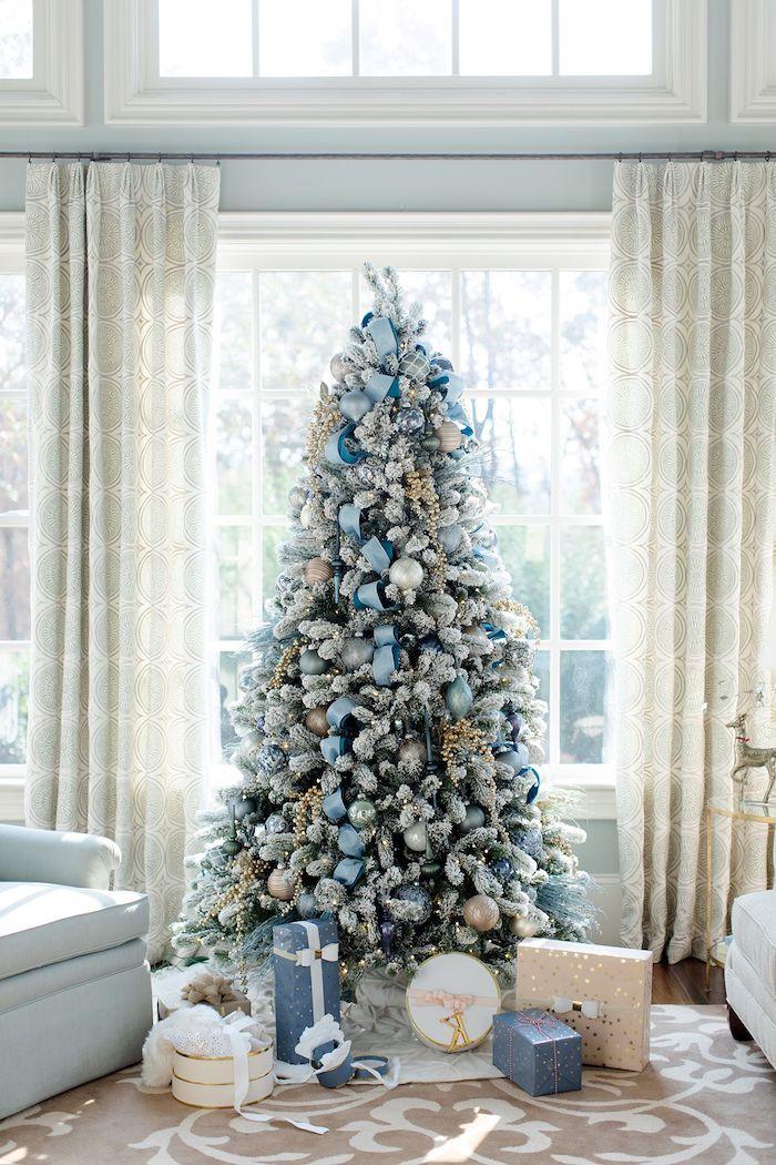 Künstlicher Weihnachtsbaum geschmückt mit weißen und hellblauen Christbaumkugeln und künstlichem Schnee
