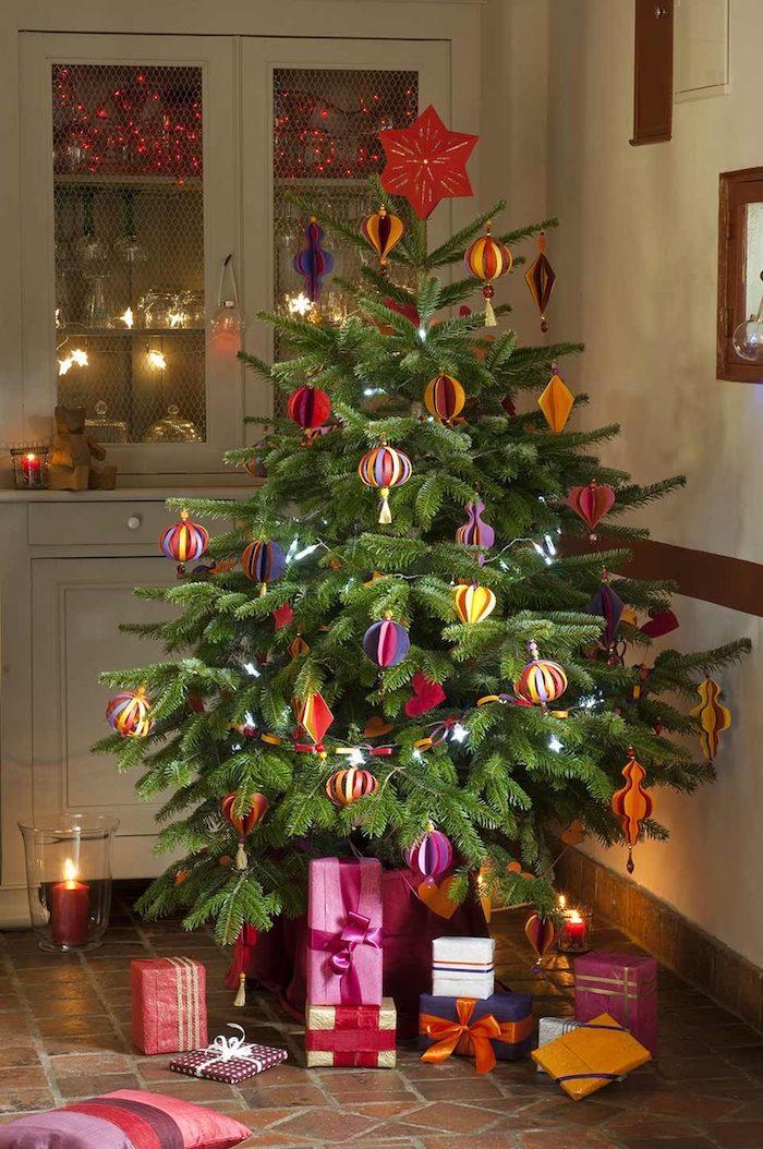 Weihnachtsbaum schmücken mit Christbaumkugeln aus Papier, Weihnachtsgeschenke verpackt mit buntem Geschenkpapier