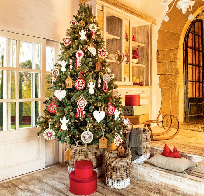 Echter Weihnachtsbaum geschmückt mit bunten Aufhängern in Form von Häuschen, Herzen und Engeln