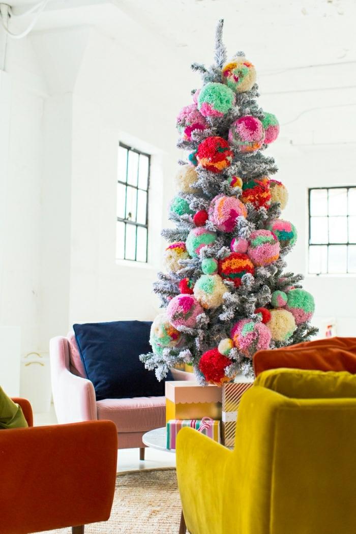 Weihnachtsbaum geschmückt mit großen bunten Pompons, Sofas in grellen Farben, Wandfarbe Weiß