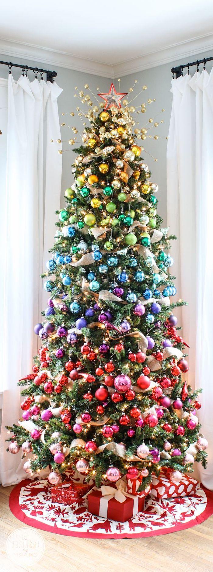 Tannenbaum mit bunten Christbaumkugeln in Schichten schmücken, Dekoband zwischen den Weihnachtskugeln, Geschenke unter dem Baum