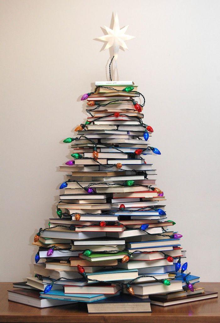 Weihnachtsbaum aus Büchern, geschmückt mit Lichterkette und Christbaumspitze, coole Alternative zum klassischen Tannenbaum