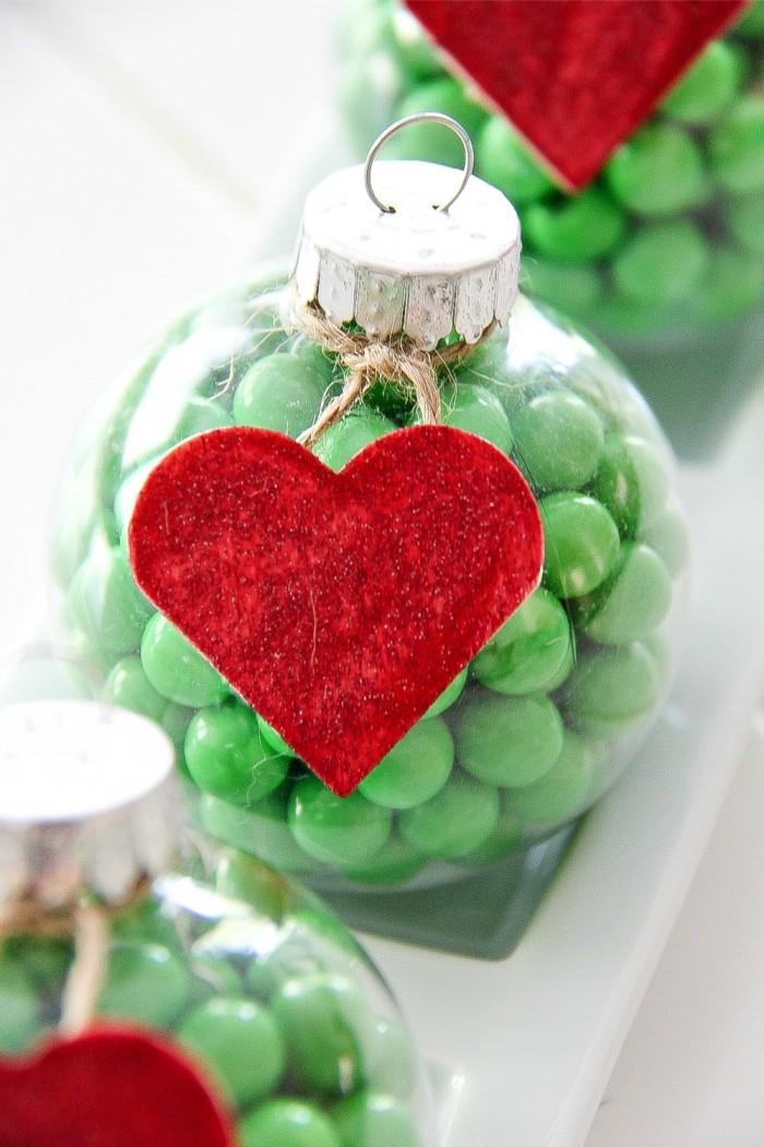 weihnachtsdeko basteln, grüne bonbons, rotes herz, transparente weihnachtskugel