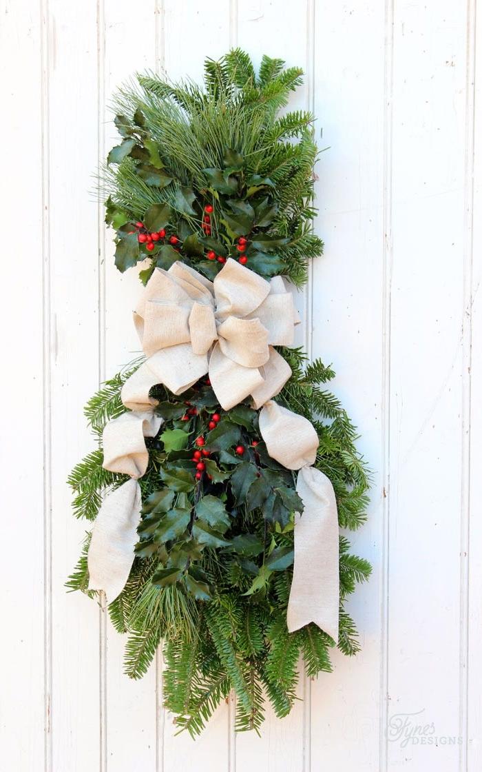 weihnachtskranz aus grünen zweigen, kleine rote früchte, weihnachtsdeko ideen, zaundeko