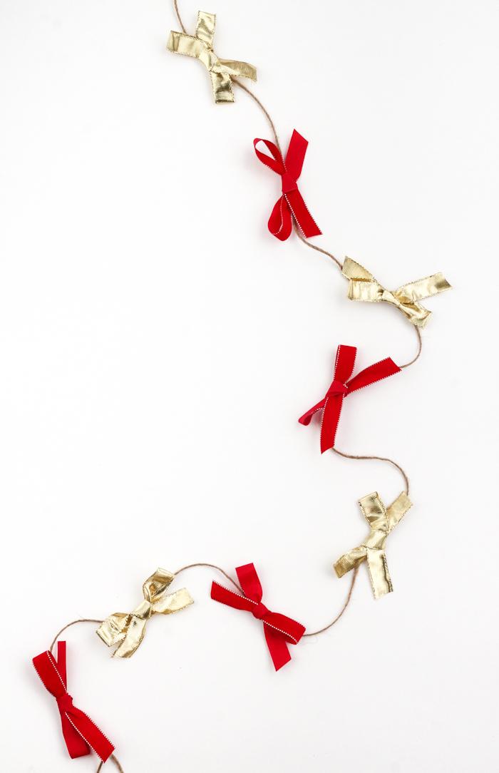weihnachtsdeko selber basteln, selbstgemachte girlande, goldene und rote schleifen