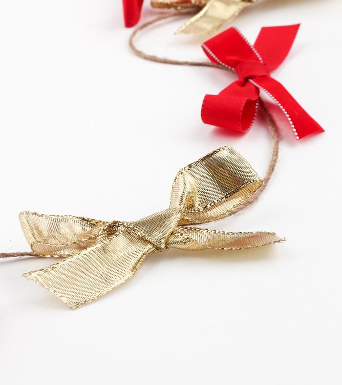 weihnachtsdeko selber basteln, girlande mit roten und goldenen schleifen, leinenschnur