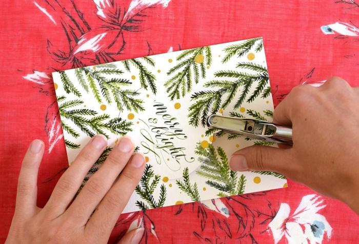 Weihnachtskarten selbst gestalten, grüne Tannenzweigen, gelbe Flecken, ein Loch bohren