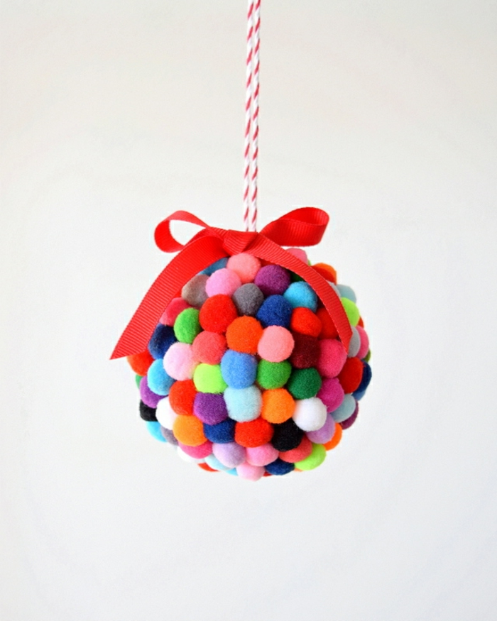 eine Kugel mit bunten Pompons, eine rote Schleife, Weihnachtskugel gestalten