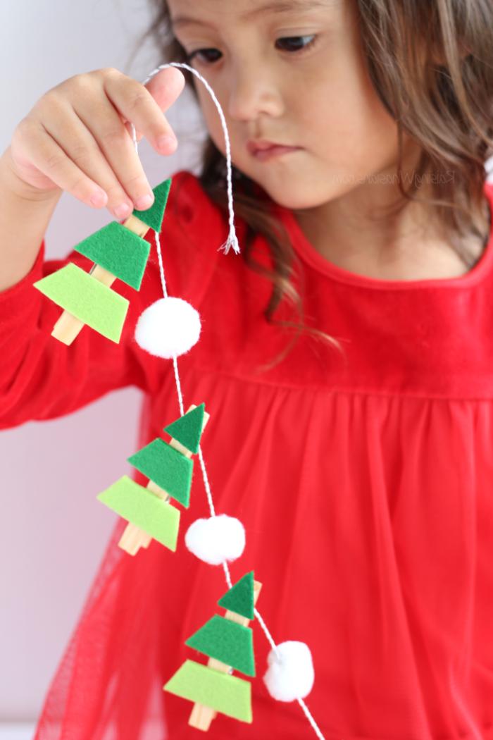 rotes kleid, kleines mädchen, weihnachtsbasteln mit kindern, girlande mit tannenbäumen