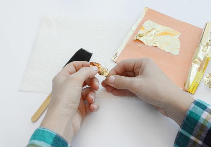die Anhänger von Weihnachtskugel mit goldener Farbe umhüllen, Weihnachtskugeln bemalen