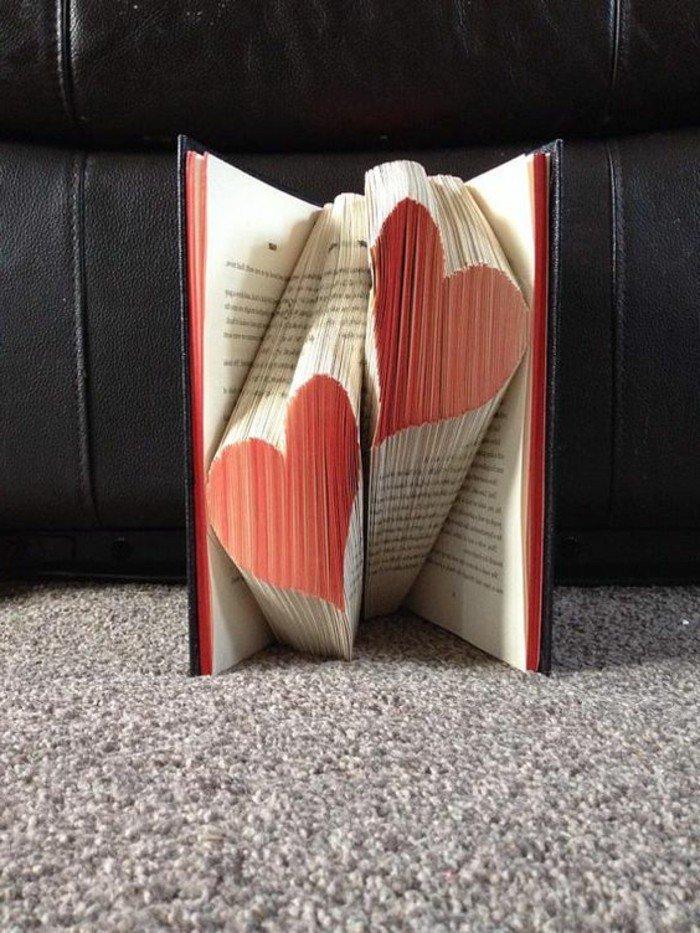 zwei Herzen in roter Farbe aus einem Buch mit roten Seiten, gefaltete Bücher zu Valentinstag