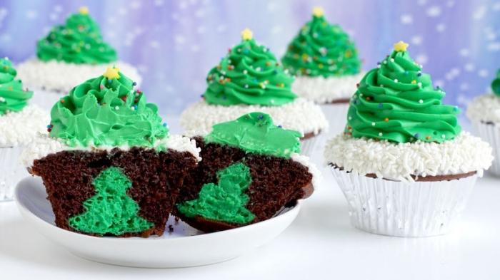 winterliche desserts, schokomuffins dekoriert mit weißer und grüner sahne, kleine weihanchtsbäume