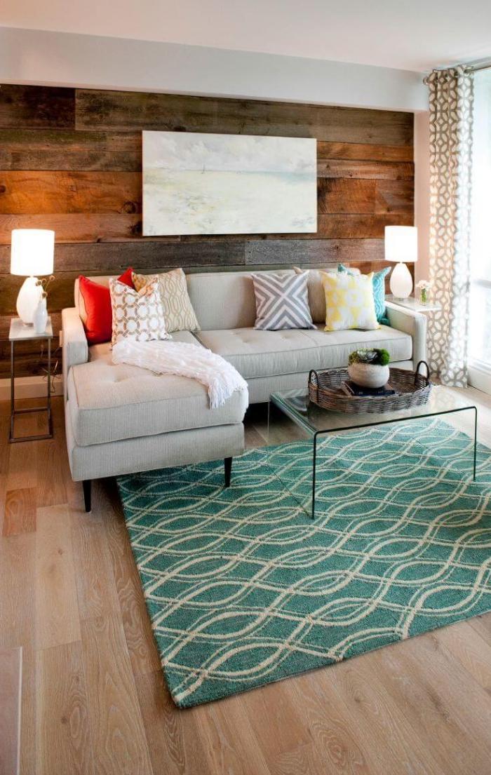 wohnung deko, teppich mit geometrischen motiven, hellgraues ecksofa, holzwand