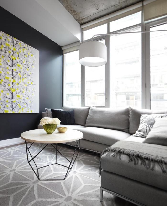 wohnzimmer gestalten, tisch mit geoemtrischen beinen, großes bild in grau und zitronengelb