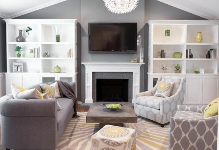graue Wohnzummermöbel mit geometrischen Motiven, ein bunter Teppich, weiße Regale